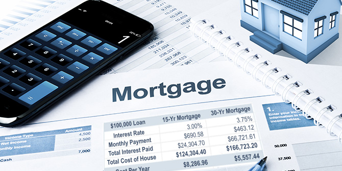 smart phone with calculator app showing, sitting on top of mortgage documents