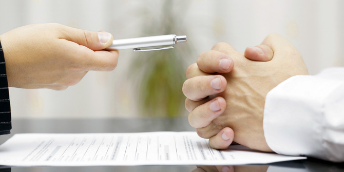 hand offering pen to a closed fist over a financial document