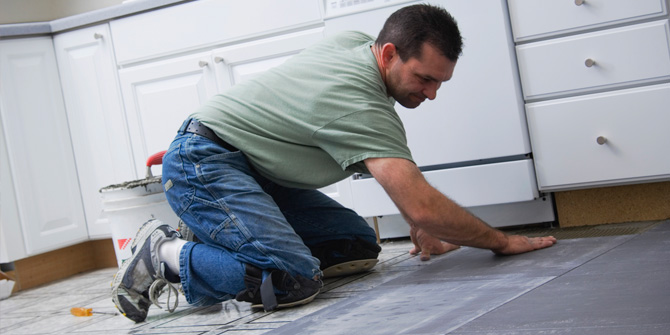 Man tiling the floor of his kitchen