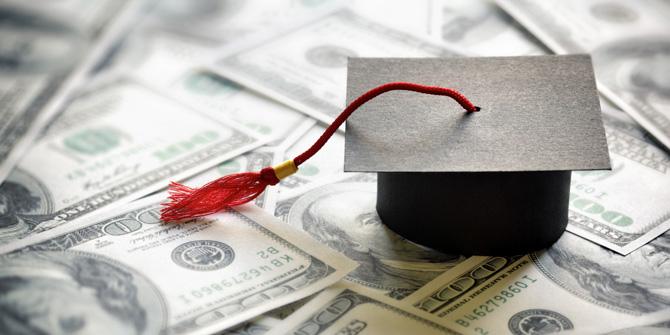graduation cap on top of pile of $100 bills