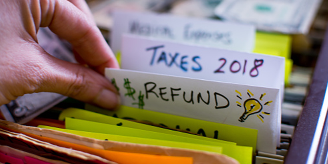 Woman pulling out file on Tax season 2018 Tax refund