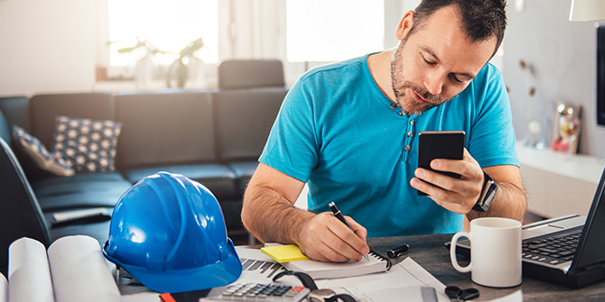Man writing notes and holding smart phone