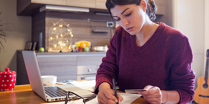 woman looking at credit card making notes on paper with laptop nearby
