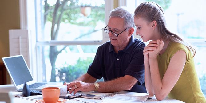 Man and teen girl talking finances