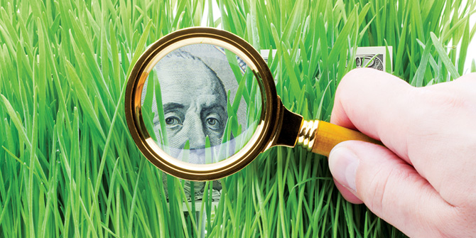 Hand holding magnifying glass over a bill in grass