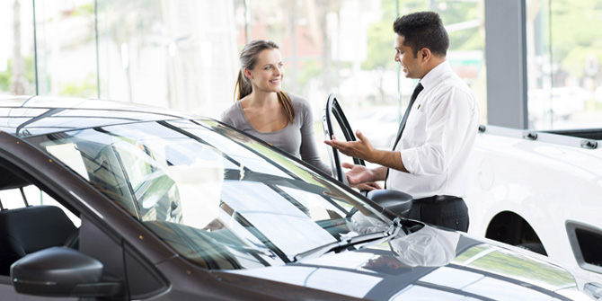 woman looking at new car with salesman