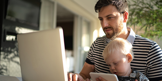 Man holding child and working on laptop