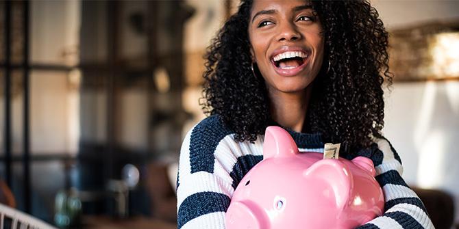 Woman hugging her piggy bank