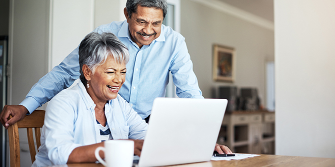 Couple smiling while looking at laptop
