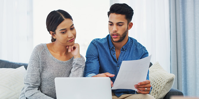 Young couple sitting on the sofa going through paperwork