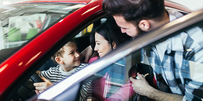 Man and woman looking at child pretending to drive a car