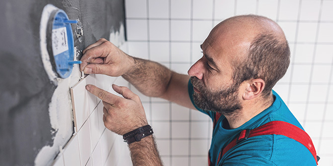 Man installing tiles on bathroom wall