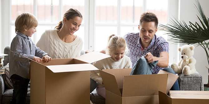 Man, woman and two children packing boxes on moving day.