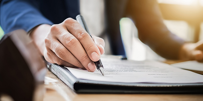 A hand signing a legal document