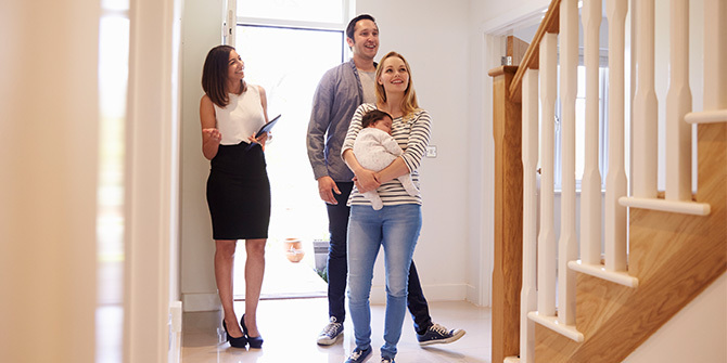 Real estate agent showing family around property for sale