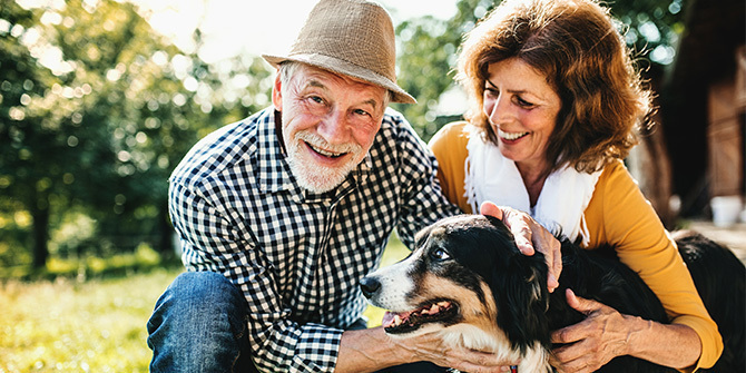 A senior couple crouching and petting a dog.