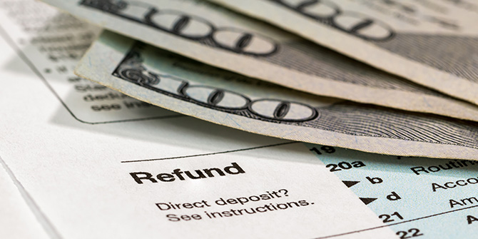 hundred-dollar bills lying on the refund section of a tax form