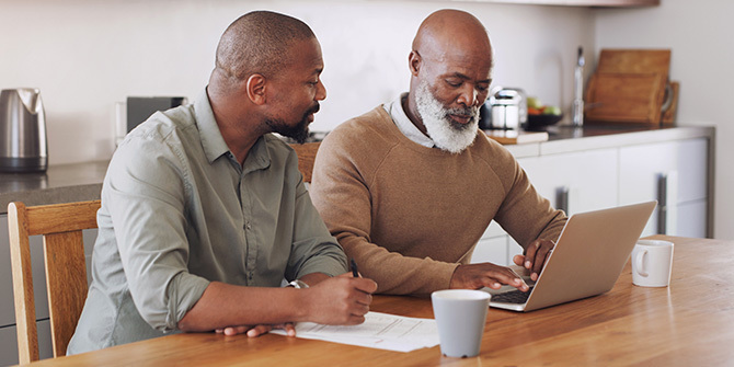 Younger man helping his father with finances