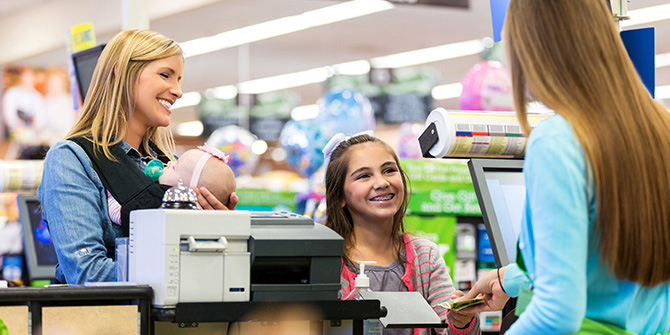 Woman holding a child while young girl pays for groceries