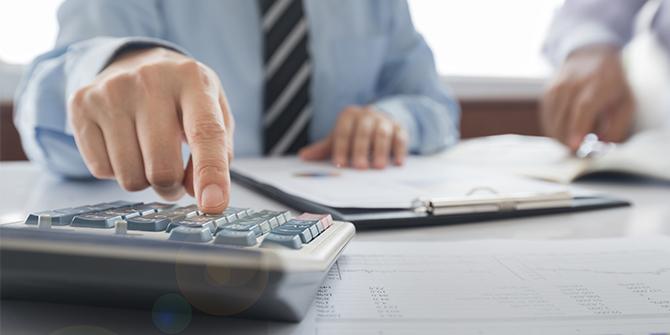 Man using calculator on a desk