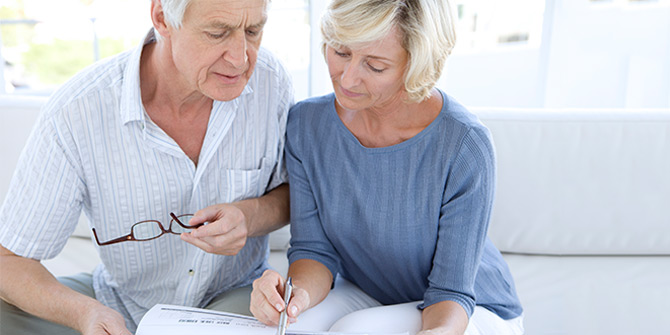 Couple sitting on couch looking over paperwork
