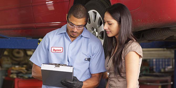 Mechanic reviewing car repairs with customer