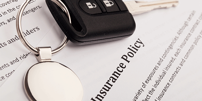 Car keys over insurance policy paperwork