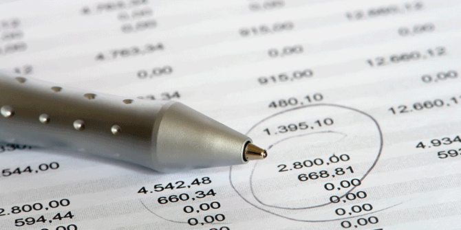 Pen sitting on printed budget chart