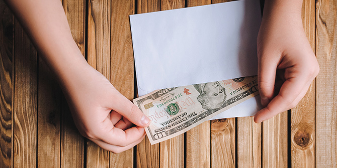 Hands taking dollars from an envelope