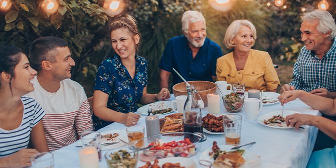 Multi-generation family having dinner in the backyard