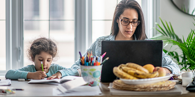 Mother works on computer while daughter works on homework