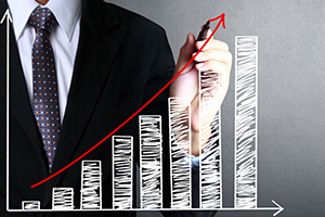 Man in suit drawing on increasing bar chart
