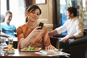 Woman at dinner looking at cellphone