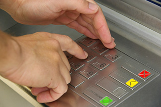 Hand on ATM keyboard