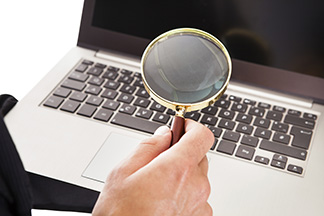 Hand holding magnifying glass over keyboard