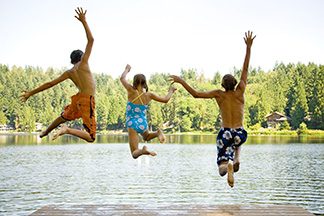 Three kids jumping into a lake.