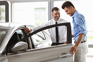 man buying a new car from a salesman