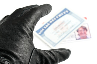 Gloved hand reaching for a Social Security card and driver's license
