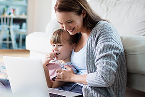 Mother and daughter using a laptop at home.