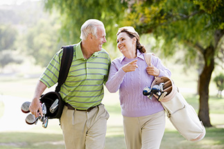 man and woman with golf bags