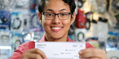 young adult holding up first paycheck