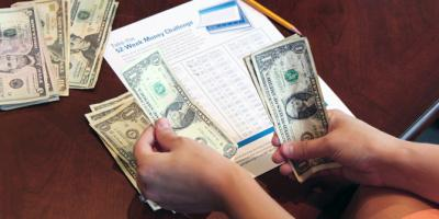 hands counting money on table in front of a 52-Week Money Challenge worksheet
