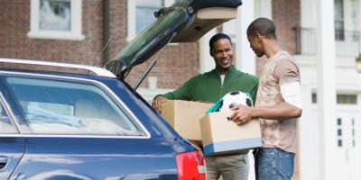 Father and son unpacking car on first day of college
