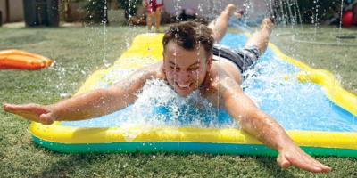 dad in back yard sliding on his stomach down a slip and slide