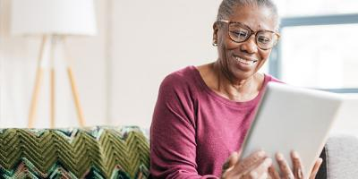 Elderly lady looking at tablet smiling
