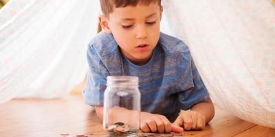 Little boy counting coins to add to a jar
