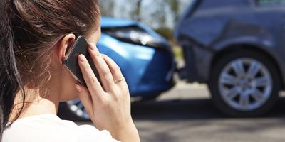 Woman holding a cellphone at the scene of a car accident