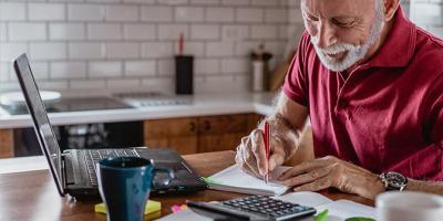 Man with open laptop, creating a budget on paper
