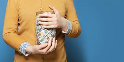 Hands holding jar full of money