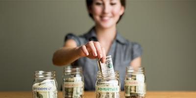 """Woman putting money into a jar labeled """"adventure"""""""